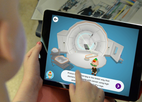 A young patient is introduced to proton therapy via the Xploro app on their tablet.